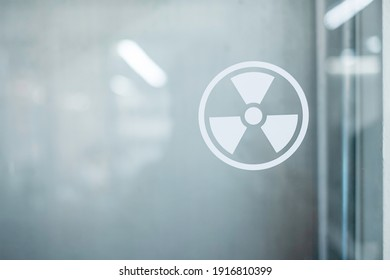 Radiation zone sign sticker on window of laboratory room. Health and safety concept