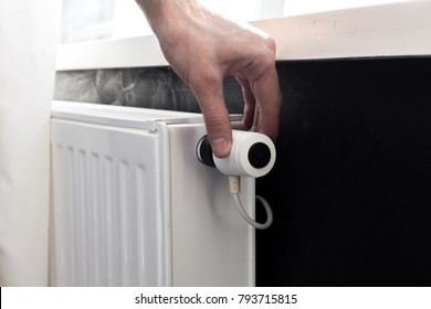 Radiator adjustment closeup. Man's hand adjusting radiator temperature.