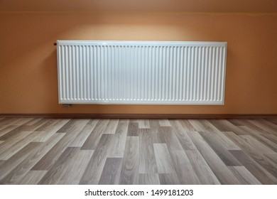 Radiator in an empty room with parquet, window light