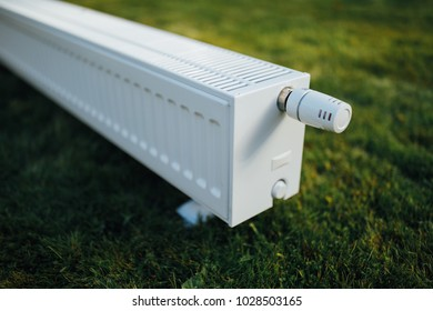 radiator on green lawn, ecological heating concept