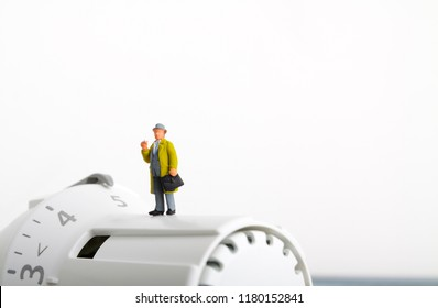 Radiator and small figurine. Businessman and heating battery. Heating season concept.