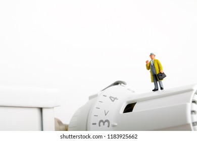 Radiator and small figurine. Businessman and heating battery.
