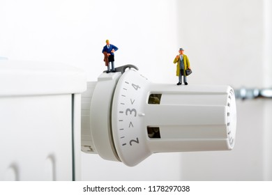Radiator and small figurines. Businessman and heating battery. Two customers or consumers and heating battery.