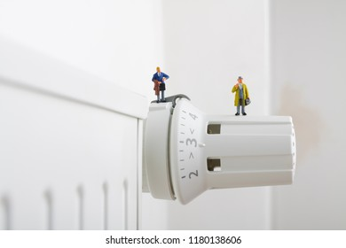Radiator and small figurines. Two businessmen and heating battery. Heating season concept.