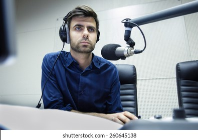 Radio anchorman hosts the evening talk-show. Young man working as a radio anchorman sitting at the radio studio and looking at the monitor.