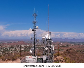 Radio communications tower on mountain with cellular attachment and town in the background