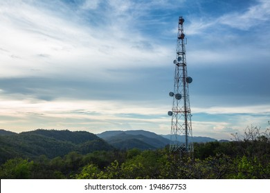 A radio communications tower at top of green mountain
