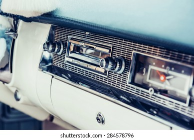 Radio in dashboard in interior of old vintage automobile.
