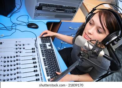 A radio DJ announces news in a studio