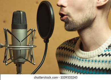 Radio dj concept. Profile portrait of handsome young man with blond hair hosting show live in studio. Close up. Indoor shot