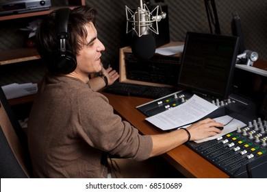 Radio DJ. Young man with microphone and headphone.