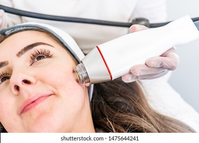 Radio frequency microneedling machine handpiece on the cheek of a woman's face during a beauty skin tightening treatment.