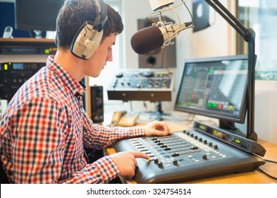 Radio host wearing headphones using sound mixer on table