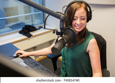 Radio Jockey Smiling While Wearing Headphones In Studio