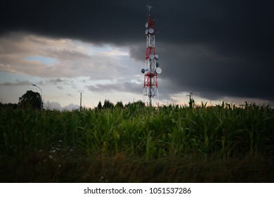 radio mast and antenna broadcast tower red and white in front of dark clouds heaven. thunderstorm clouds with a tower or receiving station on corn field