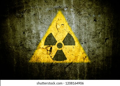 Radioactive (atomic nuclear ionizing radiation) danger warning symbol in triangular yellow shape painted on massive cracked concrete cement wall dark green grungy texture background. Nuclear concept.