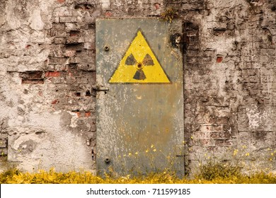 Radioactive (ionizing radiation) danger symbol painted on the old massive rusted iron door of an abandoned structure with grunge walls and overall derelict atmosphere.