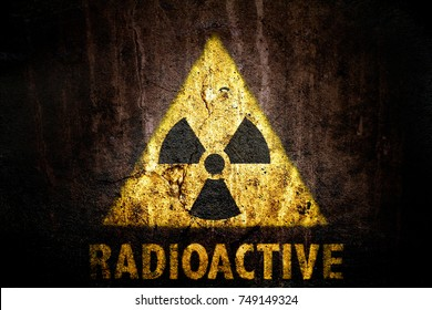 Radioactive (ionizing radiation) danger symbol with word radioactive painted on a massive cracked concrete wall with and dark rustic grunge brown texture background.