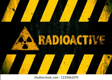Radioactive (ionizing radiation or nuclear energy) danger symbol and word with yellow and hazard black stripes painted on a massive concrete wall with dark rustic texture background with vignetting.