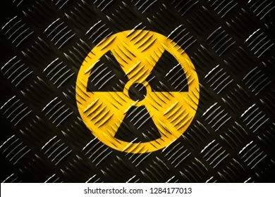 Radioactive (ionizing radiation) round yellow and black danger symbol painted on a massive steel checker metal diamond plat pattern wall with dark rustic grungy texture background.