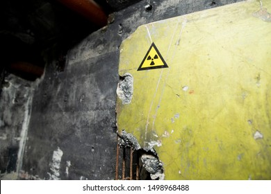 Radioactive warning on old damaged wall. Destroyed and forgotten building. Radiation symbol with russian alert. After nuclear disaster.