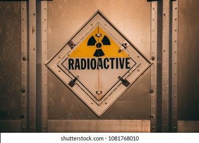 Radioactive yellow sign centered on a metal wall.