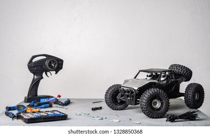Radio-controlled car models: a table with scattered tools for repairing rc buggy models and a control panel.