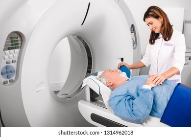 Radiographer reassuring senior man going into CT scanner in hospital