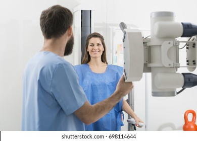 Radiologist Adjusting X-ray Machine On Female Patient At Hospita