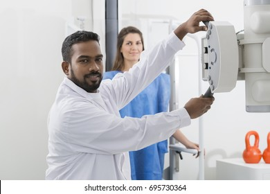 Radiologist Adjusting X-ray Machine Over Patient In Hospital