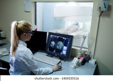 Radiologist analyzing brain MRI scan results of a patient on computer monitor in control room.