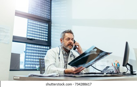 Radiologist checking a medical scan report and talking on phone. Mature doctor examining x-ray and using telephone in his clinic.