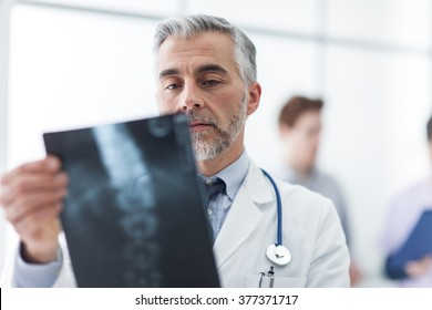 Radiologist examining a patient's x-ray, medical staff on the background, healthcare concept