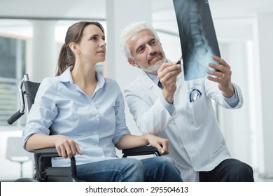 Radiologist examining a woman in wheelchair's x-ray of human spine during a visit at hospital