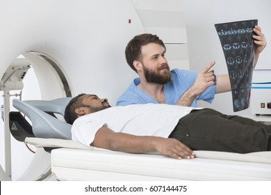Radiologist Showing X-ray To Patient Lying On CT Scanner