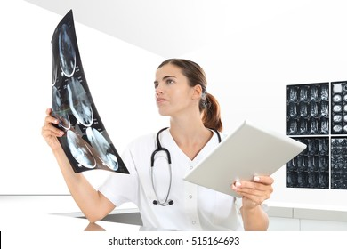 Radiologist woman checking x ray, with tablet, medical and radiology concept