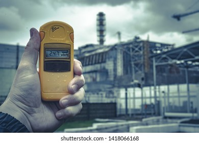 radiometer in hand with fourth Chernobyl Nuclear Power Plant reactor on the background