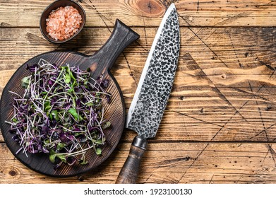 Radish microgreens, green leaves and purple stems. Wooden background. Top view. Copy space