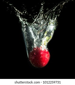 radish in water with splashes on a black background