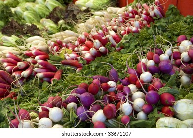 Radishes of many colors on display at a farmer's market.