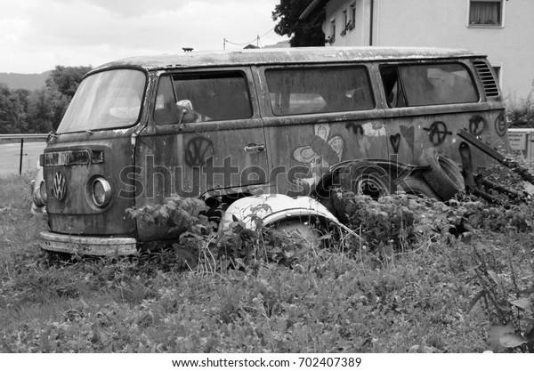Radovljica, Slovenia - August 7, 2017:  Old rusting abandoned Volkswagen Transporter Camper. Nobody in de vehicle.
