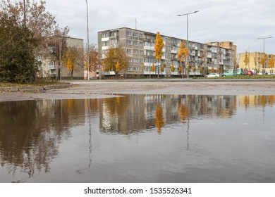 Radviliskis/ Lithuania- October 13, 2019: Typical soviet style building of one hundred flats , built in 1972. Building located in Radviliskis town Gedimino street number 1 . House reflection on puddle