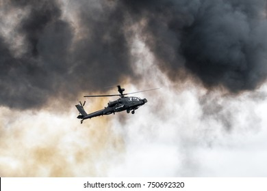 RAF FAIRFORD, GLOUCESTERSHIRE, JULY 2017: Side view of an AugustaWestland Apache gunship against a white sky and heavy smoke after simulating a ground attack.