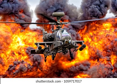RAF Fairford, Gloucestershire, UK - July 16, 2017: A British Army Air Corps AgustaWestland Apache AH1 attack helicopter hovers in front of a wall of flame at the Royal International Air Tattoo 2017