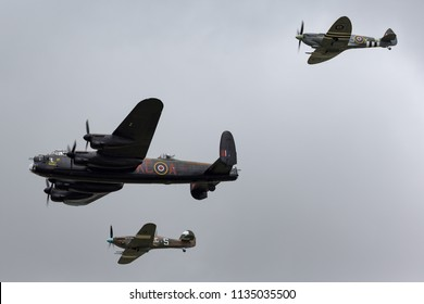 RAF Fairford, Gloucestershire, UK - July 13, 2014: Royal Air Force (RAF) Battle Of Britain Memorial Flight Avro Lancaster bomber PA474 in formation with a Supermarine Spitfire and a Hawker Hurricane.
