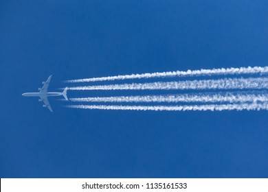 RAF Fairford, Gloucestershire, UK - July 10, 2014: Lufthansa Airbus A340 large airliner flying at high altitude with a large contrail behind it.