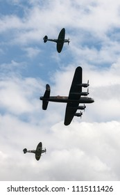 RAF Waddington, Lincolnshire, UK - July 5, 2014: Royal Air Force (RAF) Battle Of Britain Memorial Flight Avro Lancaster bomber PA474 flying in formation with two Supermarine Spitfire fighter aircraft.