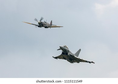 RAF Waddington, Lincolnshire, UK - July 6, 2014: Supermarine Spitfire from the Royal Air Force Battle of Britain Memorial Flight leads a RAF Eurofighter Typhoon FGR4 fighter aircraft in formation.