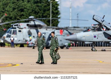 RAF Waddington, Lincolnshire, UK - July 7, 2014: Two Royal Air Force Pilots walking across the tarmac at RAF Waddington with aircraft sitting in the background.