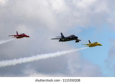 RAF Waddington, Lincolnshire, UK - July 6, 2014: Former Royal Air Force (RAF) Hawker Hunter T.7A G-FFOX leading a formation of two Folland Gnats.